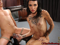 Simone Kross takes her slave down from his standing bondage and ties him to a chair so she can hang heavy weights from his balls as she teases him with her naked body. She flogs his cock and body, then releases his hand and instructs him to stroke his cock. Unable to cum, she locks him into chastity and sends him home.